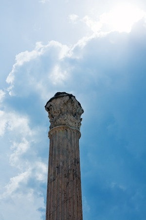 single antique marble column on background of cloudy blue sky