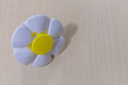 Plastic flower placed on soft wooden grain background Stock Photo - 87205419