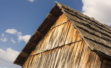 Old barn roof against a blue sky with fluffy clouds