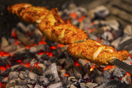 Chicken kebab being cooked over charcoal