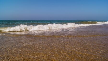 beautiful pebbles beach with waves and blue sky