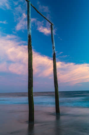 wooden poles on the beach at sunset glow