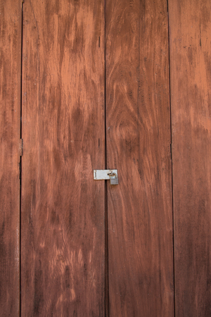 Vintage brown wooden locked door with old door knob Stock Photo