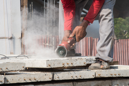 plasterwork: Builder worker with grinder machine cutting concreate floor at construction site Stock Photo