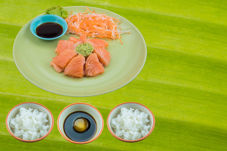 Salmon sashimi with sauce on green ceramic plate and Raw Egg in soy sauce on green leaf banana Stock Photo