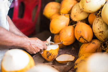 Orange fresh coconut peeling and shelling with heavy chop knife for juice in Male,Maldives Stock Photo