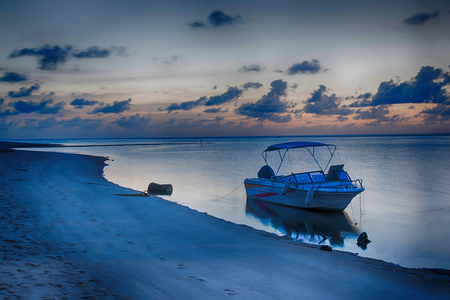 Boat floating in sea at the beach,Colorful sunset with boat ot the river bank.