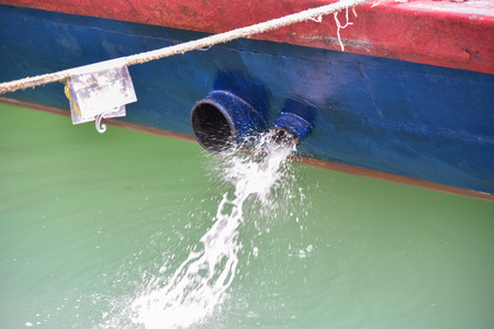 Fishing boat releasing excess water from its ballast. Stock Photo