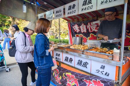 Fukuoka, JAPAN - 15 October 2019 :Traditional some meat skewers being grilled in a barbecue, in Japan at street food vendor market.