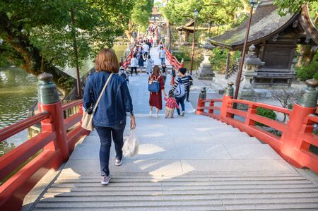 Fukuoka, JAPAN - 15 October 2019 : Tourists walking along the bridge. Arched bridge and historic shrine, Red bridge in Dazaifu Tenmangu, Fukuoka, Kyushu, Japan.