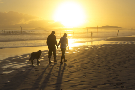 relaxing beach: Beautiful beach sunset with silhouette of couple walking their dog at Strand beach, Helderberg, Cape Town, Western Cape, South Africa. Stock Photo