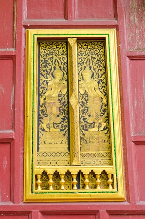 Ancient Golden carving wooden door of Thai temple in Bangkok, Thailand