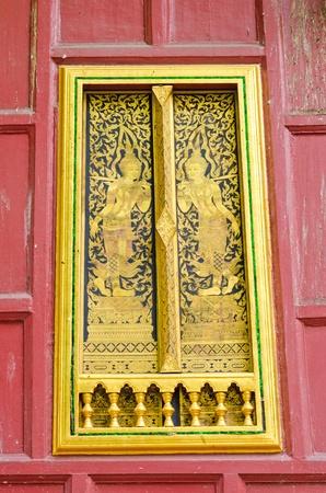 Ancient Golden carving wooden door of Thai temple in Bangkok, Thailand