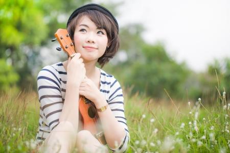 Asian young women hug her ukulele in meadow