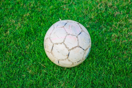 Old ball on beautiful green grass, sport photo
