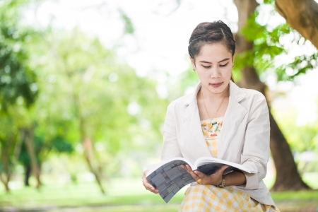 College student reading a book in park Stock Photo