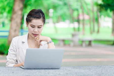 Young business asian woman with laptop, serious