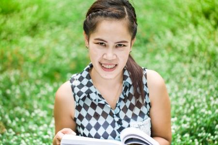 Beautiful asian girl holding an open book, read background summer green park