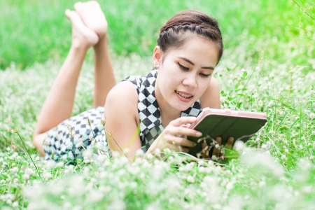 Beautiful Young Woman use Tablet Computer In Park, ehite flower  Stock Photo - 20383574