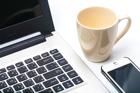 Close up coffee cup with laptop and cell phone
