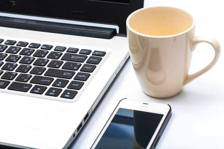 cafe bombon: Cierre de la taza de café con el ordenador portátil y el teléfono celular Foto de archivo