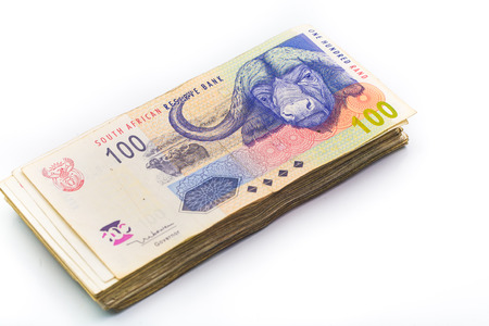 rand: Scattered pile of bundled south african rand bank notes on an isolated background