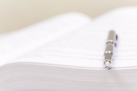 Close-up of open book and pen, White