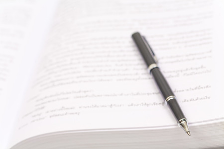 Close-up of open book and pen on white Stock Photo
