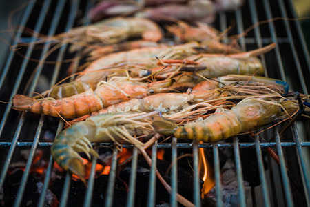 delicious prawn spit on grill with flames in background, closed up