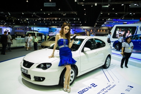 proton: NONTHABURI - DECEMBER 8: Unidentified modellings posted over  The new Proton gen 2 display on stage at The 30th Thailand International Motor Expo on December 8, 2013 in Nonthaburi, Thailand.