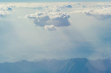 Wolken und Himmel von oben durch das Fenster eines Flugzeugs gesehen