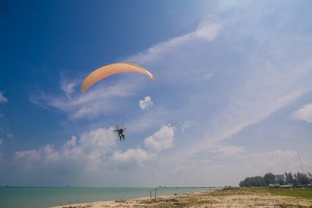 Flying paramotor under blue sky, beach photo