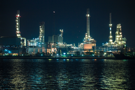 scenic of petrochemical oil refinery plant shines at night, closeup near river