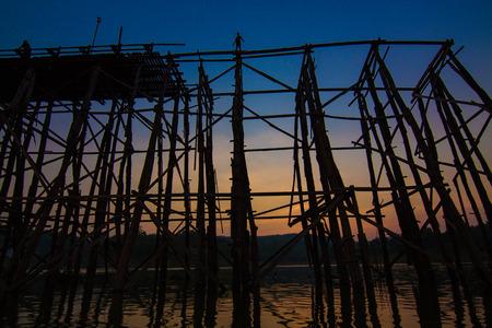 The silhouette of old wooden bridge Bridge collapse Bridge across the river and Wood bridge (Mon bridge )at sangklaburi, kanchanaburi photo