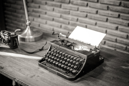 Black and white of an old typewriter with paper on a wooden table, photo in retro style