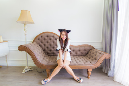 Young asian smile woman sitting on a couch in modern room .Fashion photo.