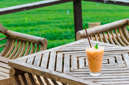 Cup of fresh sweet tea background of tea plantations on wood table photo