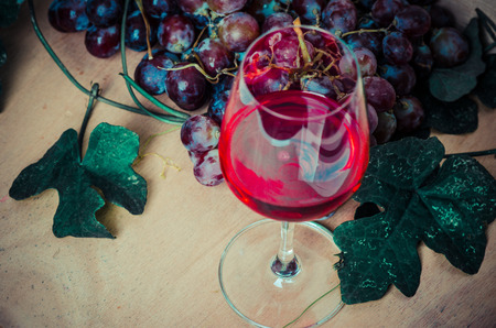 Red wine and red grapes on wood background, the still life with red wine photo