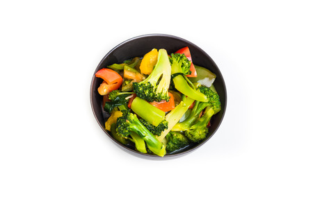 fresh vegetables in plate isolated on white background, black bowl photo