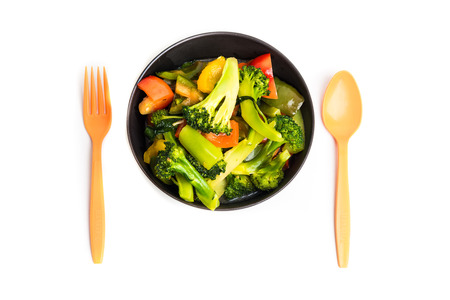 fresh vegetables in plate with spoon and fork isolated on white background, black bowl photo