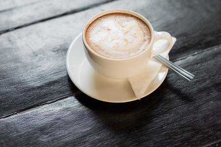 Tasse Kaffee auf Holztisch mit Kaffeelöffel und Papierserviette