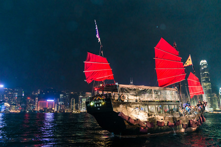 drove: HONG KONG - Dec 7: Victoria Harbor on December 7, 2014 in Hong Kong. An old chinese junk departed from Ocean Terminal and drove across Victoria Harbor.
