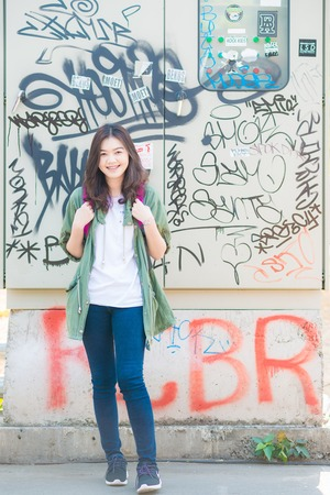 knapsack: Young beautiful asian woman posing against wall with graffiti, Woman with knapsack Editorial