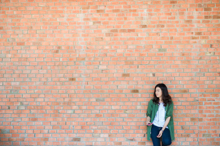 Young asian woman wear green coat stand in front of brick wall backround, Hipster woman