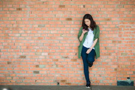 City lifestyle stylish hipster girl using a phone texting on smartphone app in a street in front of red brick wall 스톡 콘텐츠