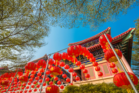 chinese red lanterns hanging in street for new year celebrating against blue sky at chinese temple