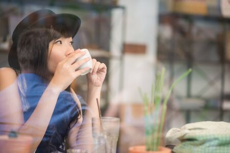 Hipster asian woman drinking coffee in cafe through mirror Stock Photo
