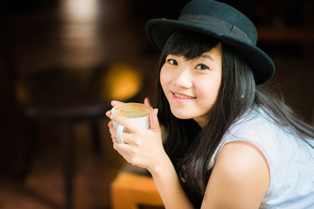 Asian young woman holding coffee cup smiling looking at camera, Close up on face at coffee shop Stock Photo