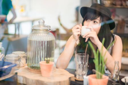 internet cafe: Hipster asian woman drinking coffee in cafe through mirror Stock Photo