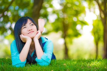 girl lying down: beautiful asian girl  lying down on green grass. Beautiful relaxing lying in the garden